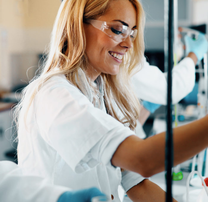 Attractive female student of chemistry working in laboratory